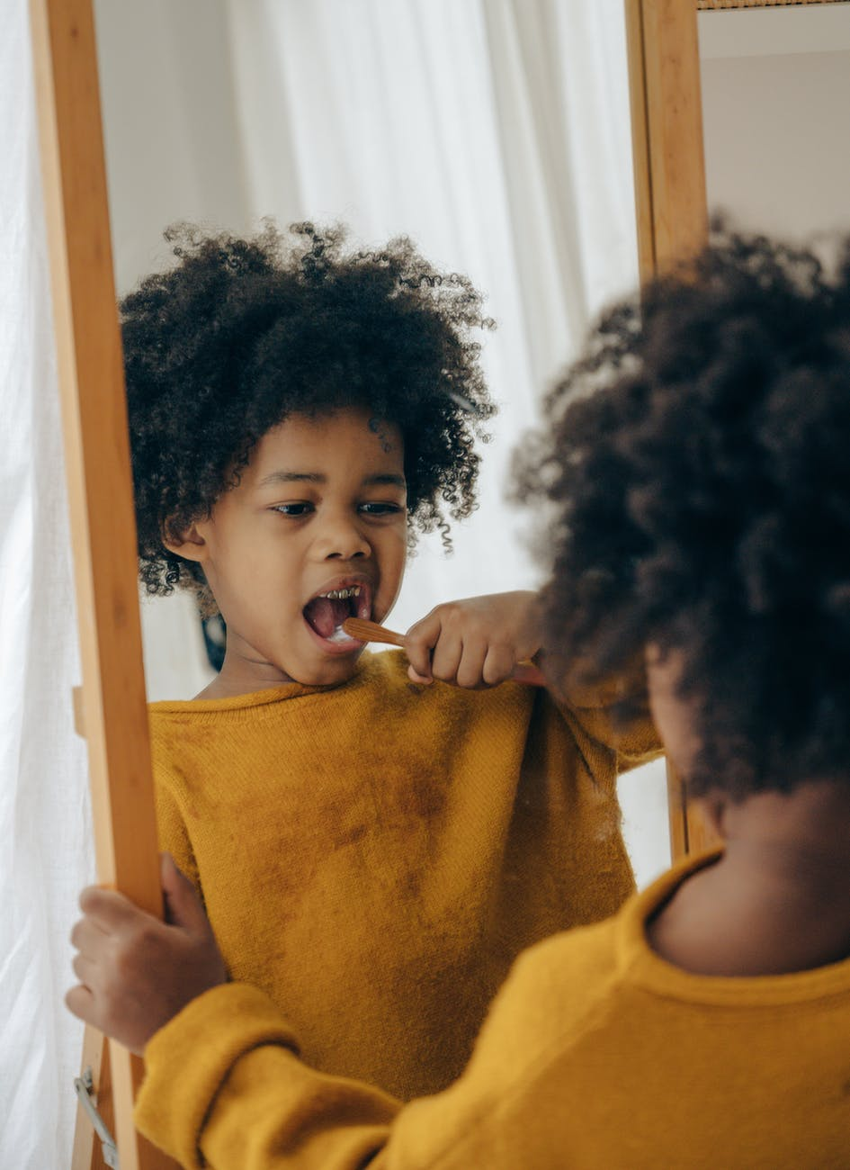 funny boy brushing teeth in morning